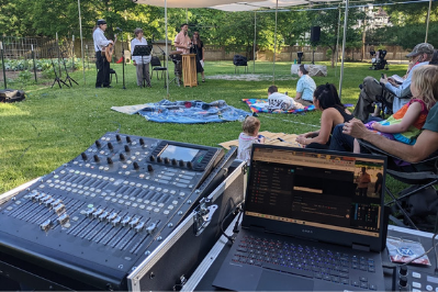 From the perspective of an A/V volunteer running the service: in the foreground, a computer and mixing board. In the background, Rabbis lead the congregation in a Friday service outside under the sukkah