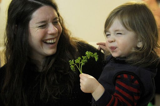 NICK SCHNELLE/JOURNAL STAR  From left, Rabbi Karen Kriger Bogard laughs as her nineteen-month-old son Gavi squints after tasting parsley on Monday during a Seder ceremony in the Bogard home. A Seder is a Jewish ritual feast that marks the beginning of the Jewish holiday of Passover.
